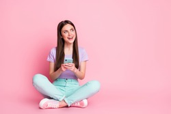 Full size photo of excited girl sit floor legs crossed use cellphone enjoy texting typing social network feedback wear turquoise violet purple trousers isolated pastel color background