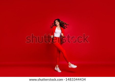Full size photo of fancy girl touching her modern jacket turning around looking isolated over red background