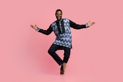 Full size photo of friendly black man dancing over pink studio background, copy space. Cheerful african american guy wearing traditional costume and showing welcoming gesture, studio shot