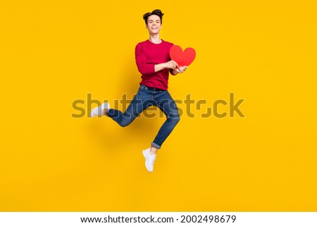 Full size photo of funny brunet young guy jump hold heart wear red sweater jeans isolated on yellow color background Stock photo ©