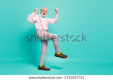Full size photo of funny excited grandpa raise fists leg celebrate senior meeting party wear specs pink shirt suspenders bow tie pants shoes yellow socks isolated teal color background