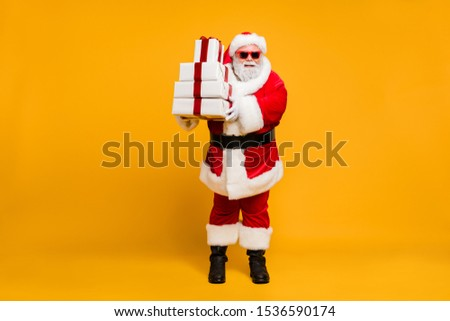 Full size photo of funny funky santa grey-hair claus in red hat headwear hold christmas packages from magic north pole on x-mas noel night celebration isolated over bright color background #1536590174