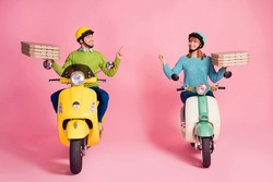 Full size photo of funny lady guy drive two vintage moped carry paper pizza boxes direct finger empty space courier wear casual outfit headgear isolated pink color background