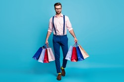Full size photo of handsome business man successful worker carry bags buy clothes vacation shopping center wear specs shirt suspenders pants boots socks isolated pastel blue color background