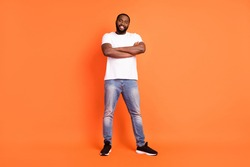 Full size photo of happy dark skin young happy man good mood smile hold arms crossed isolated on orange color background