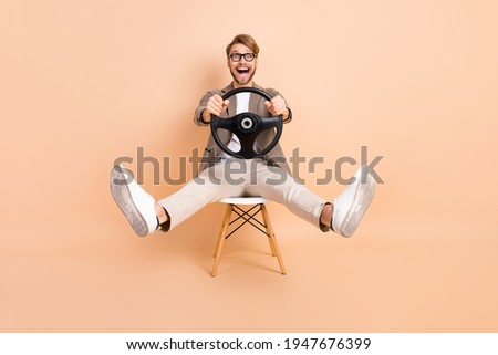Full size photo of happy excited crazy attractive man in glasses riding car fast extreme isolated on beige color background