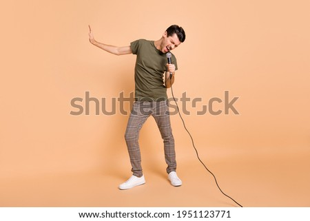 Full size photo of hooray brunet guy sing in mic wear t-shirt trousers sneakers isolated on beige color background Stock photo ©