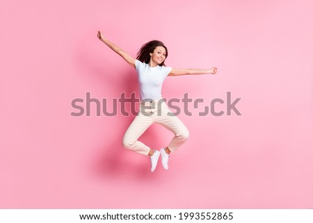 Full size photo of hooray nice brunette hair lady jump wear t-shirt pants isolated on pink background