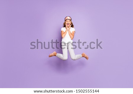 Full size photo of impressed beautiful excited blonde hair  model kid wakeup hear wonderful morning news scream wow omg jump high wear white t-shirt pants isolated over violet purple color background