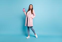 Full size photo of lovely cute cheerful girl having walk promenade holding mug wearing coat denim jeans isolated over blue background