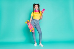 Full size photo of nice brunette girl stand on skate hold telephone headphones wear yellow t-shirt jeans sneakers isolated on cyan background
