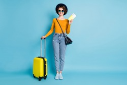 Full size photo of optimistic brunette short hairdo lady stand with bag tickets wear shirt jeans sneakers isolated on blue color background