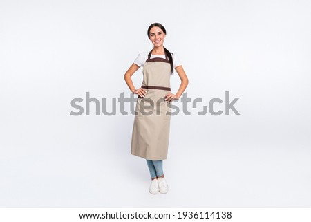Full size photo of optimistic nice brown hair lady stand wear t-shirt apron isolated on grey color background ストックフォト ©