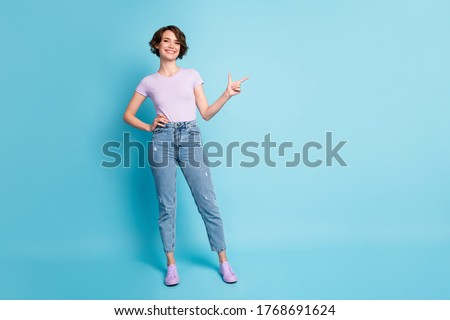 Full size photo of positive girl promoter point index finger copyspace indicate adverts promotion wear good look lilac outfit isolated over blue color background Foto stock ©