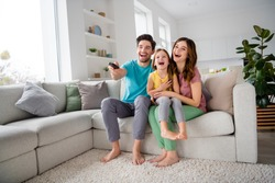 Full size photo of positive three people mom dad preteen little kid girl sit comfort couch rest watch comedy cartoon remote control switch joy laugh in house indoors