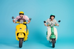Full size photo of rushing funny two people lady guy drive retro moped big speed travelers easy way good mood formalwear clothes protective caps isolated blue color background