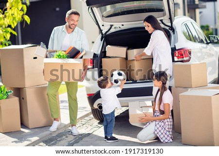 Full size photo of smiling happy family moving pack stuff dad mom and sister watch little boy put ball in automoble outside outdoor Zdjęcia stock ©
