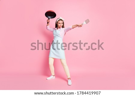 Full size photo of strong chef woman hold frying pan spatula attack enemies wear shirt pants trousers isolated over pastel color background Stock photo ©
