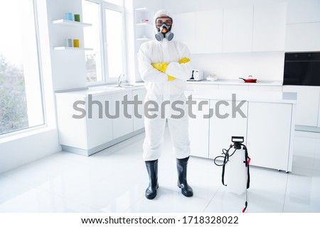 Full size photo of successful guy cleaner protective hazmat suit gloves goggles cross hands ready stop covid spread epidemic influenza infection wear boots latex gloves goggles in house kitchen
