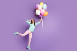 Full size photo of surprised feminine girl get present many baloons flying sky she catch impressed scream wow omg wear pink pants trousers pastel turquoise jumper isolated purple color background