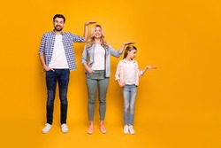 Full size photo of three members family mom dad daughter not believe quick growing up measuring length height good mood wear casual outfit isolated yellow color background