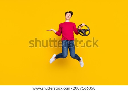 Full size photo of unsure brunet young guy jump hold wheel wear red sweater jeans isolated on yellow color background Stock photo ©
