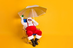 Full size photo of white grey hair bearded santa claus sit chaise-lounge raise alcohol glass x-mas christmas eve noel time relax wear hat pants isolated bright shine color background