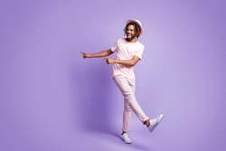 Full size photo of young afro funky crazy smiling man guy male pointing fingers in copyspace isolated on violet color background