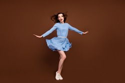 Full size photo of young attractive girl wind blow air hold arms isolated over brown color background