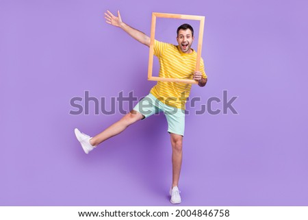 Full size photo of young excited man happy positive smile fooling snapshot frame isolated over violet color background Foto stock ©