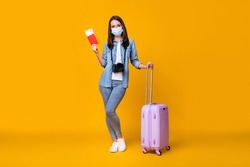 Full size photo of young lady journalist rolling bag photographer travel abroad airport quarantine registration tickets wear facial mask casual clothes isolated yellow color background