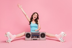 Full size photo of young smiling excited woman girl hold hand sit floor boombox wear rollers isolated on pink color background