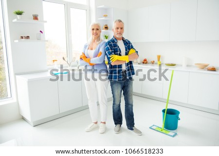 Full size portrait of attractive cleanly neat cheerful stylish couple of senior in colorful protective gloves standing with crossed arms after cleaning, looking at camera, having mop, bucket #1066518233