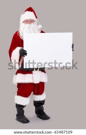 Full size portrait of Santa holding blank white board, looking at camera, isolated on gray background.?