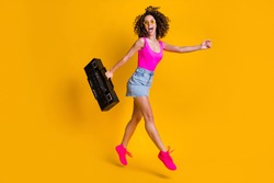 Full size profile photo of attractive curly lady hold retro boom box students event holiday jump high walk beach wear sun specs pink singlet denim skirt shoes isolated yellow color background