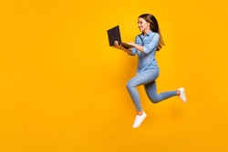 Full size profile photo of beautiful business lady jump high hold notebook hands hurry work browsing laptop wear casual denim outfit white sneakers isolated yellow color background