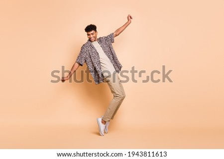 Full size profile photo of brunet optimistic guy dance wear modern shirt trousers sneakers isolated on beige color background Stock photo ©