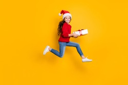 Full size profile photo of crazy little lady jumping high taking giftbox from santa in x-mas midnight wear red knitted pullover and jeans isolated yellow background