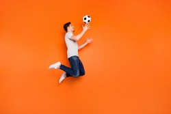 Full size profile photo of funky guy jump high up catch football ball addicted fan goalkeeper wear striped t-shirt jeans sneakers isolated bright orange color background