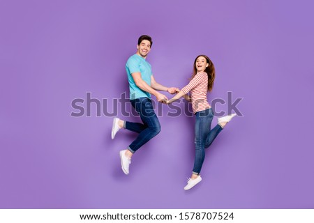 Full size profile photo of funky two people guy lady jumping high holding hands having fun feelings wear casual blue striped t-shirts jeans shoes isolated purple color background #1578707524