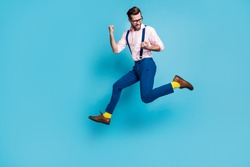 Full size profile photo of handsome man jump high up running competition raise fists first place winner race marathon wear specs shirt suspenders pants boots isolated blue color background
