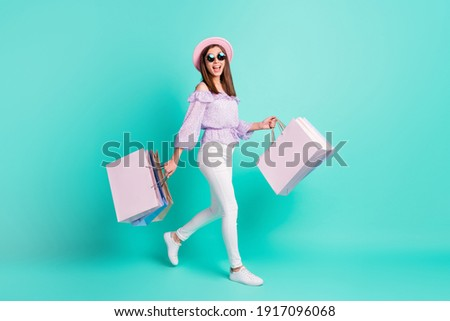 Full size profile photo of optimistic nice brunette girl going hold bags wear purple shirt cap trousers sneakers isolated on blue background