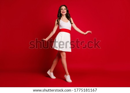Full size profile photo of pretty lady good mood beaming smile walking down street summer time rejoicing make step wear white short dress shoes isolated red color background