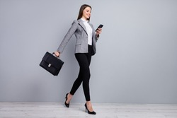 Full size profile photo of slim pretty business lady young chief hold diplomat bag browsing telephone go meeting wear plaid blazer trousers high-heels isolated grey color background