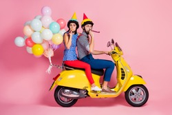 Full size profile side photo funny carefree two people motorcyclists driver drive fast speed motorbike whistle blower travel anniversary event have air baloons fly isolated pink color background
