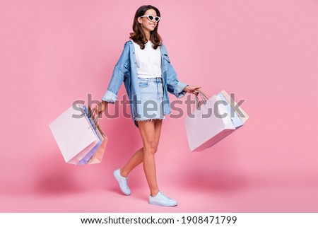 Full size profile side photo of charming woman go copyspace friday shopping hold bags isolated on pink color background