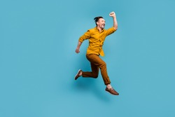 Full size profile side photo of cheerful crazy man cant wait black friday bargains jump hurry run fast wear good looking outfit sneakers isolated over blue color background
