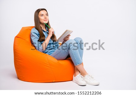Full size profile side photo of focused girl sit on lounge chair think want create fiction story feel curious try guess ponder wear denim clothes sneakers isolated over white color background