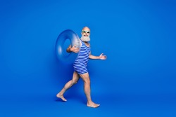 Full size profile side photo of grey haired elderly man walk beach summer hold ring wear sunglass isolated on blue color background