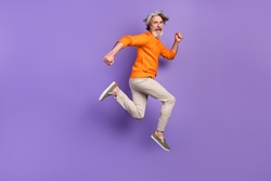 Full size profile side photo of mature man happy positive smile go walk run jump hurry sale isolated over purple color background